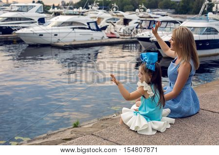little girl three years sitting with mom with long blond hair and they are dressed in blue dress and large blue bow on her head , sitting at the pier on the sea with a yacht during sunset