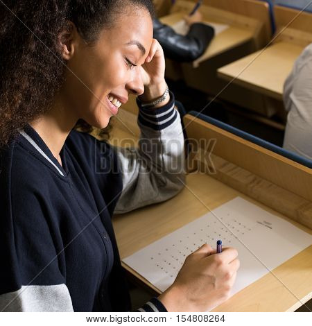 Close-up of happy student writing easy exam