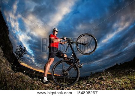 Sportive man with bicycle against sunset and cloudy sky
