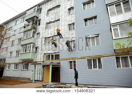 Repair and restoration of a facade of a building. Home facade insulation. Group of workers installs panels siding on a wall of a house