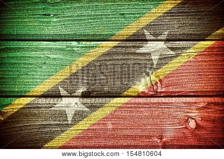 Flag of Saint Kitts and Nevis painted on old grungy wooden background: 3d illustration