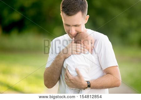 Portrait of young happy man holding his newborn cute babe dressed in white unisex clothing. Caucasian father embracing tenderly his adorable new born child and smiling. Outdoors shot