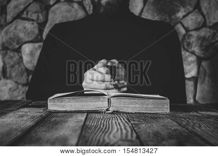 a man in black clothes with a prayer beads in hand praying in front of an old open book. the concept of praying and studying. selective focus black & white photo