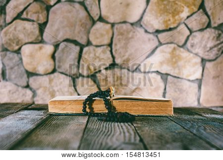 prayer beads with a cross on an open old book on old wooden table on a background of stone walls. selective focus toning photo. with space for your text