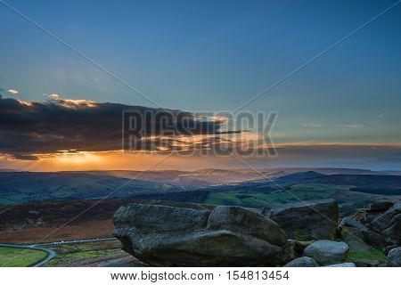 Stanage Edge Sunset, which is located in the Peak District National Park in England. Stanage Edge is the largest of the gritstone edges that overlook Hathersage in Derbyshire