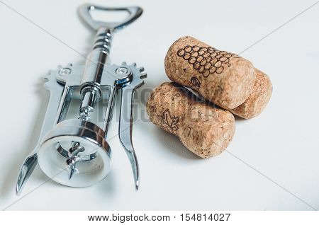 corkscrew and corks lies on a table-top.