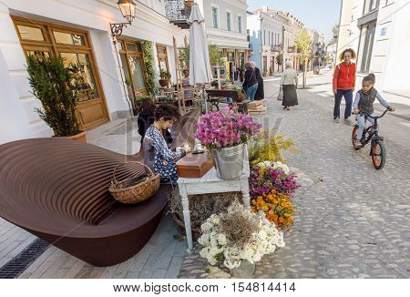 TBILISI, GEORGIA - OCT 9, 2016: People with children walking on historical street with outdoor flower shop on October 9, 2016. Tbilisi has a population of 1.5 million people