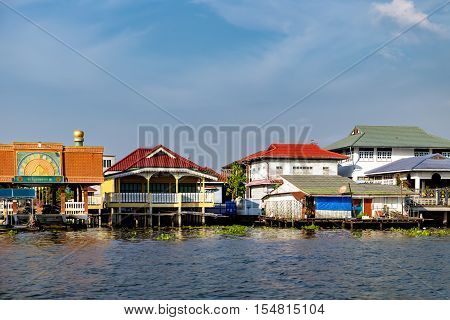 Bangkok, Thailand - December 8, 2015: Small pier for boats and Thai traditional houses on the bank of Chao Phraya River Bangkok Thailand. Village riverfront in Bangkok Thailand.