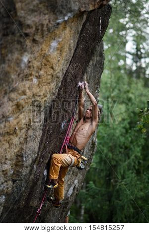 Male rock climber struggles to reach his next grip on a steep cliff. Extreme sport.