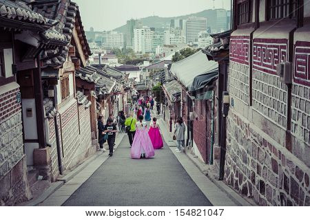 SEOUL - SOUTH KOREA - OCTOBER 21 2016 : A couple women wander through the traditional style houses of Bukchon Hanok Village in Seoul South Korea.