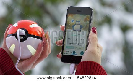 Samara, Russia - November 1, 2016: woman playing pokemon go on his iphone. pokemon go multiplayer game with elements of augmented reality. Catching the Snorlax pokemon.
