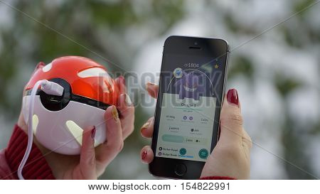 Samara, Russia - November 1, 2016: woman playing pokemon go on his iphone. pokemon go multiplayer game with elements of augmented reality. Catching the Gengar pokemon.