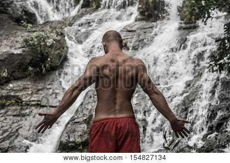 Back view of muscular man wearing red shorts standing with raised arms near waterfall. Male tourist enjoying by a water fall in forest