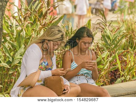 PORTO GALINHAS, BRAZIL, JANUARY - 2016 - Two girls teen sitting at park watching his cellphones in Porto Galinhas a watering place located in Pernambuco Brazil
