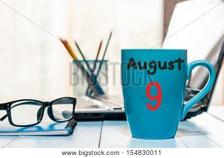 August 9th. Day 9 of month, morning coffee cup with calendar on business office background. Summer time. Empty space for text.
