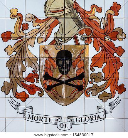 Lisbon, Portugal - Nov 10, 2016: Ceramic tile in Lisbon street Portugal emblem of fire brigade. Inscription - Victory or death