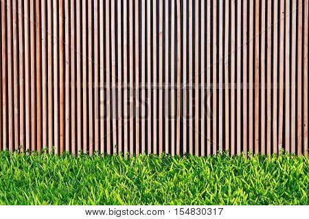 Wooden wall slat in household with green grass. use to be background for put some stuff on wooden slat.