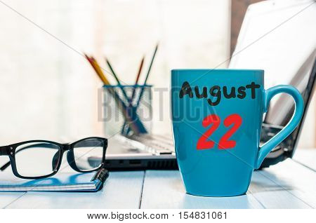 August 22nd. Day 22 of month, morning coffee cup with calendar on HR office background. Summer time. Empty space for text.