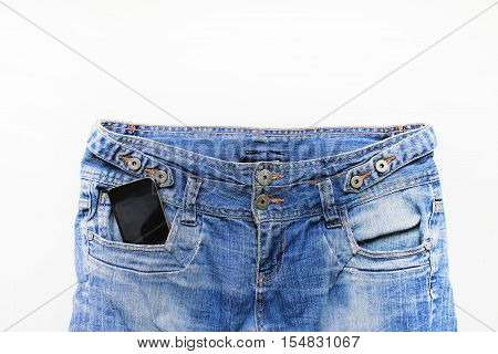 Mobile cell phone smartphone in blue denim jeans pocket close up detail isolated on white background with empty copyspace for text. Technology, communication lifestyle concept