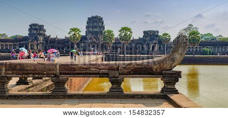Siem Reap, Cambodia - February 1, 2016: Unidentified tourists visit to Angkor Wat temple Siem Reap Cambodia. Naga serpent cobra king Vasuki in the foreground guards the entrance to the bridge.