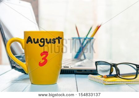 August 3rd. Day of the month 3, morning yellow coffee cup with calendar on business workplace background. Summer time. Empty space for text.
