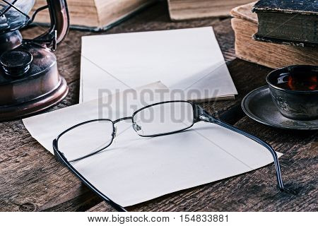 Desk with paper sheets, books, lamp, teacup and eyeglasses on the rustic wood table