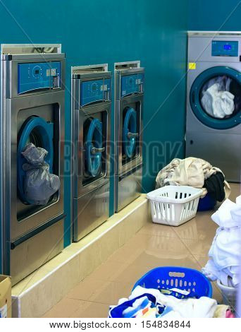 Several washing machines in a public laundry.