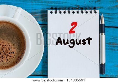 August 2nd. Day 2 of month, loose-leaf calendar on blue background with morning coffee cup. Summer time. Unique top view.