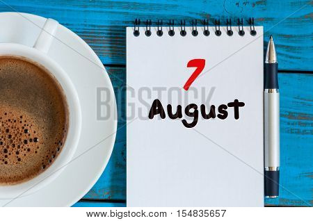 August 7th. Day 7 of month, loose-leaf calendar on blue background with morning coffee cup. Summer time. Unique top view.