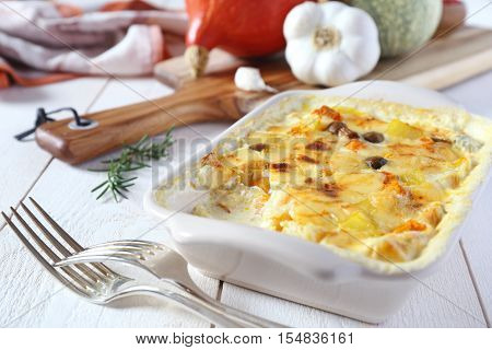 Pumpkin gratin with cheese and mushroom  in ceramic dish