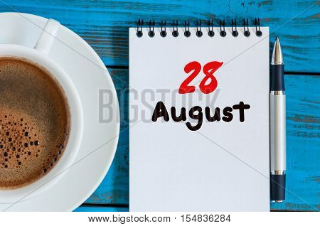 August 28th. Day 28 of month, loose-leaf calendar on blue background with morning coffee cup. Summer time. Top view.