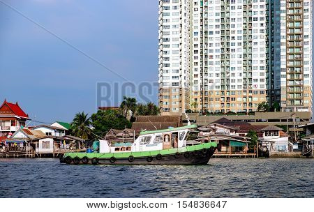 View of the Chao Praya river with its boats traffic. Old and new Bangkok in one urban landscape.