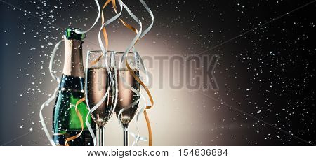 Green bottle of champagne, wineglasses with silver and golden ribbons