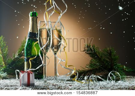 Festive Christmas composition with champagne glasses, gift and snow