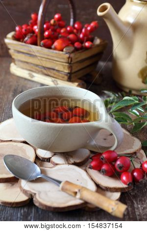 Rosehip tea and berries in basket and teapot