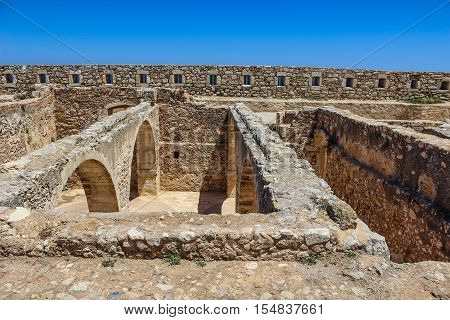 The stone constructions into ancient fortress. Walls with loopholes. Arched transition.