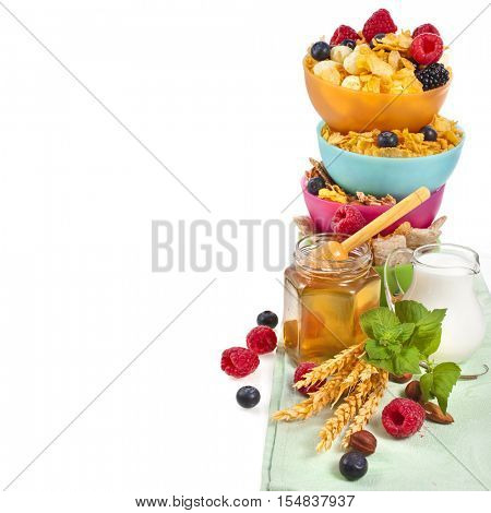 Tower stack of colorful plastic bowl with fresh berries, honey and corn flakes isolated on white background