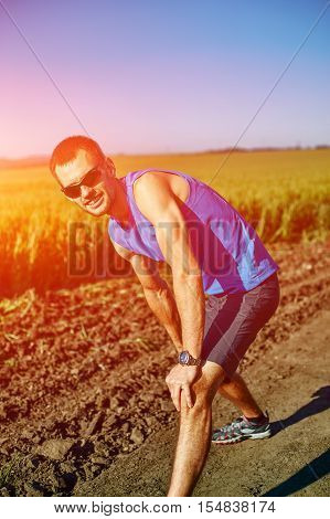man runner athlete warming up before jogging along a green field in the early morning. man lunged forward on one knee. athlete feels pain in knee. man fitness sunset jogging workout wellness concept.