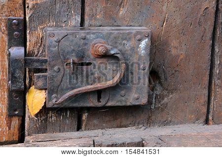 Old door latch on medieval wooden door and fallen yellow leaf in Bulgaria