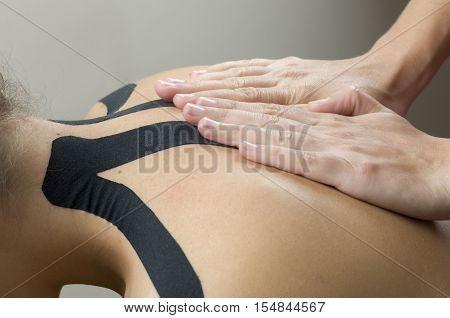 Physiotherapist Putting On Black Kinesio Tape On Woman Patients Back
