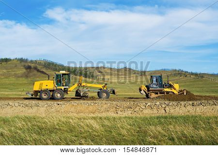 Grader and bulldozer on the construction of the road in the steppe