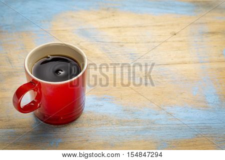 red stoneware cup  of black coffee against grunge wood with a copy space