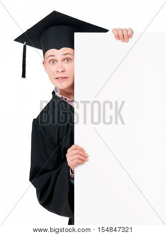 Male graduate student peeking from behind a blank panel. Portrait of happy handsome guy in graduation gown with placard board, isolated on white background. Young man holding empty banner.