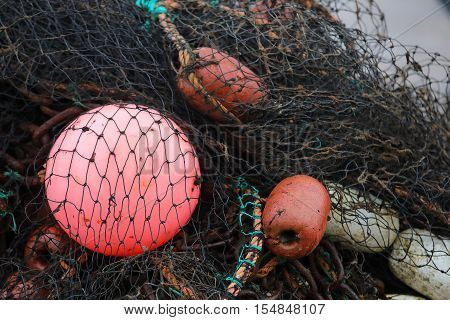 Black fishing net red and white buoys
