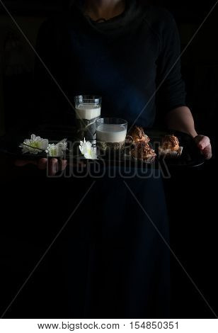 still life in the small Dutch-style. woman's hands holding a tray. cakes and milk.