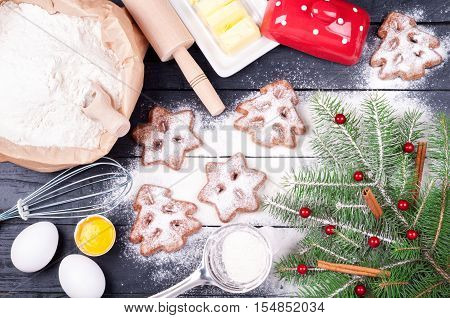 Ingredients for cooking Christmas baking with flour eggs butter and kitchen utensils - rolling pin and whisk. Homemade baked Christmas cookies on wooden background. Christmas background. Top view