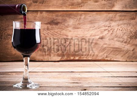 Red wine. Pouring red wine into wine glass on old rustic wooden boards. Wine background. Copy space for your text