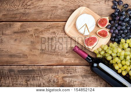Red wine grapes cheese camambert and figs on old rustic wooden table. Food background. Wine and delicatessen. Top view. Copy space