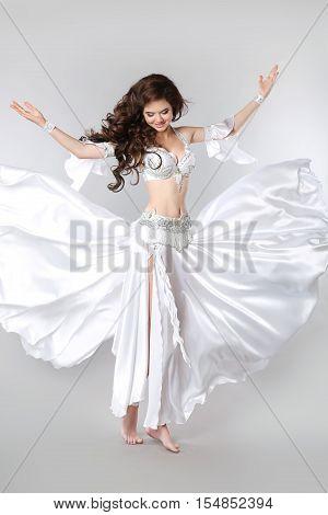 Belly Dance. Bellydancer. Beautiful Brunette Arabian Woman Dancer With Long Curly Hair Posing In Blo