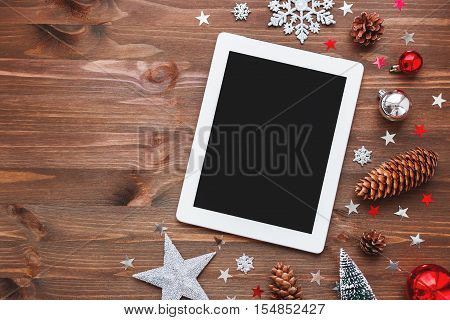 Christmas and New Year background with tablet and decorations. Place for text. Mock up flat lay top view.